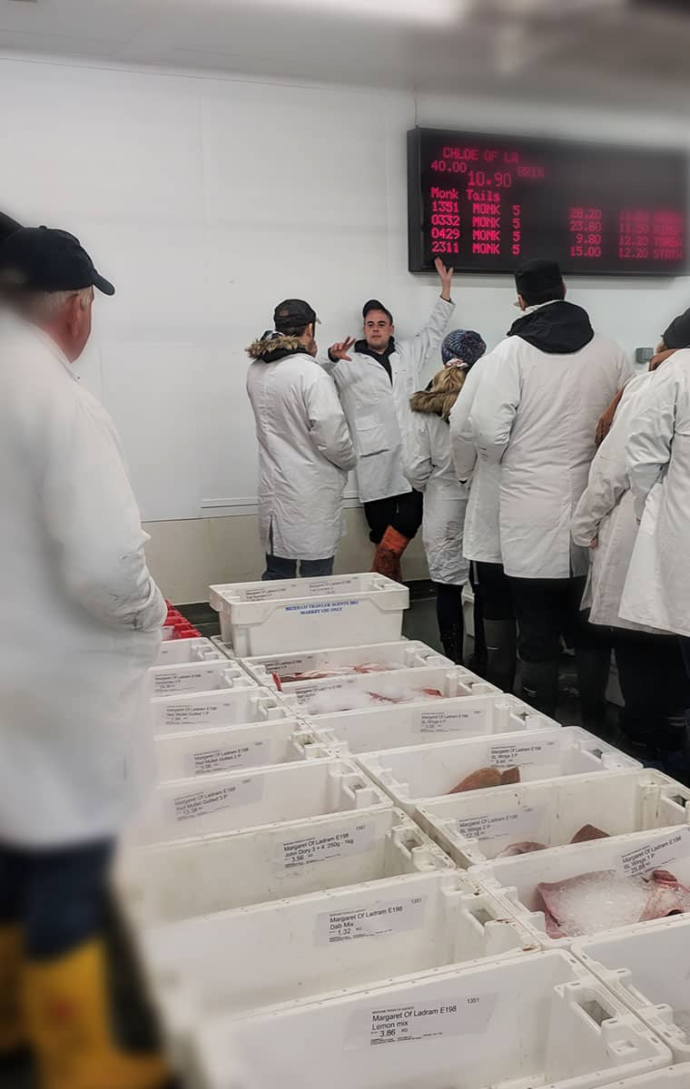 Transferring the fish sold at Brixham Fish Auction to the buyers fish boxes